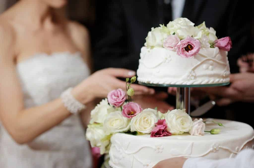 bride-and-groom-closeup-cutting-wedding-cake-at-reception
