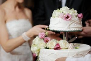 bride-and-groom-closeup-cutting-wedding-cake-at-reception