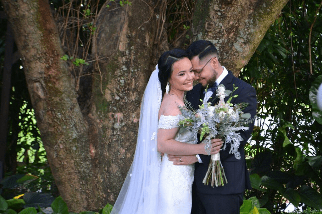 Bride and groom hugging in front of a tree