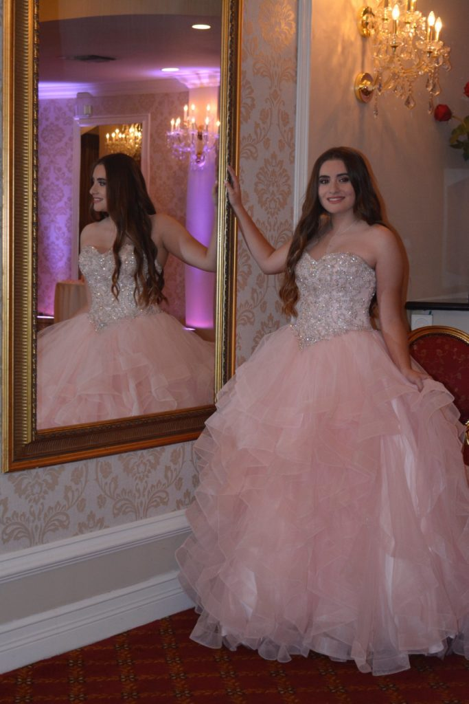 Birthday girl taking a photo next to a decorative mirror