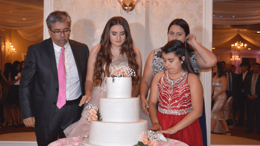 Girl standing next to a birthday cake with her family