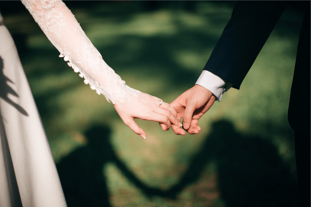 A married couple holding hands at a wedding