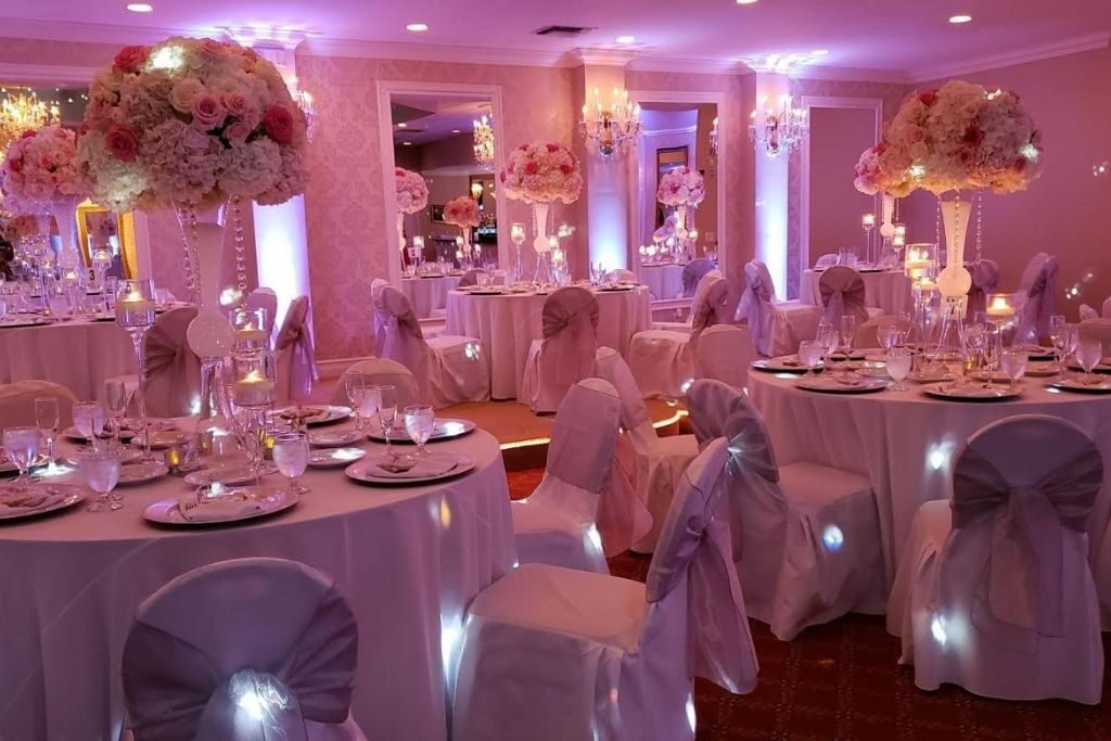 A wedding reception ballroom with tables and flower decorations