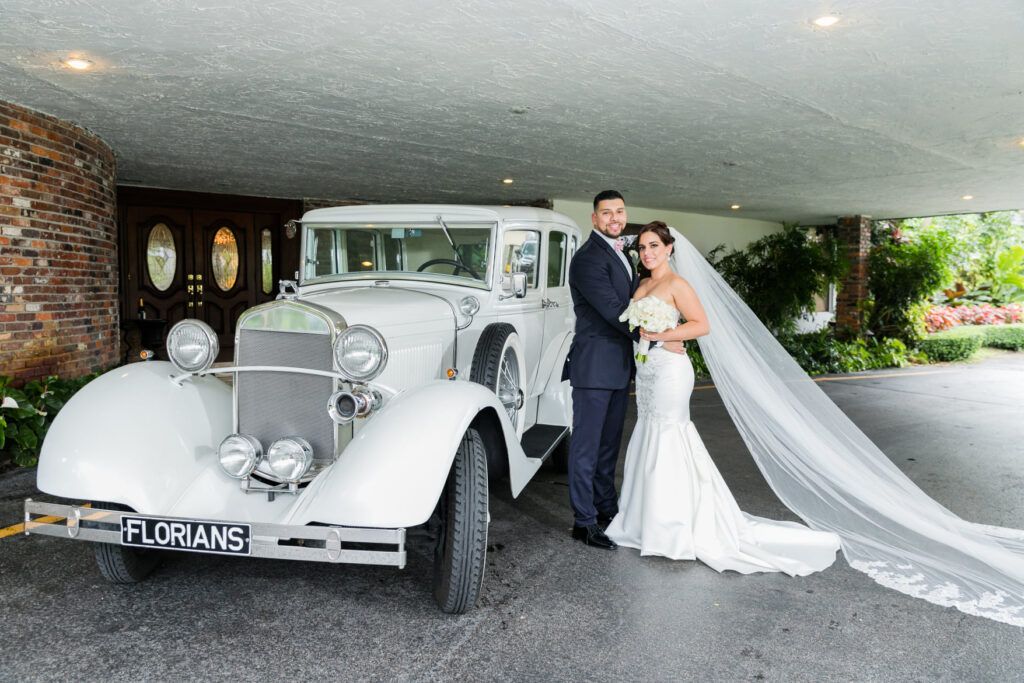 A couple getting married and standing next to a classic car for a photo